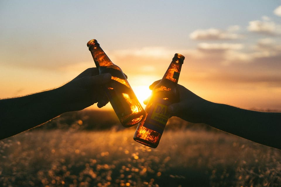 making a toast with beer bottles