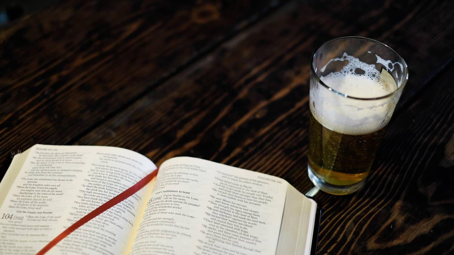 book and a glass of beer on a table