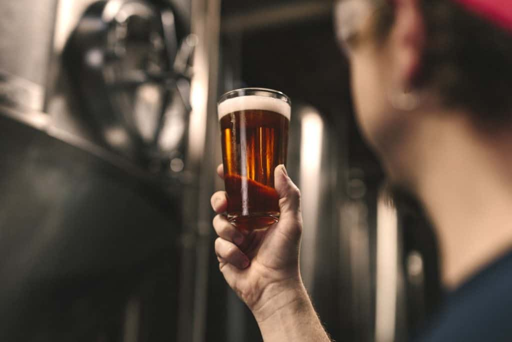 man holding a glass beer